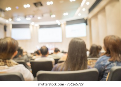 Blurred focus. Audience listening speaker making speech with big LED presentation screen on stage in conference hall, seminar or meeting room, view from listener people. Education and business backgro