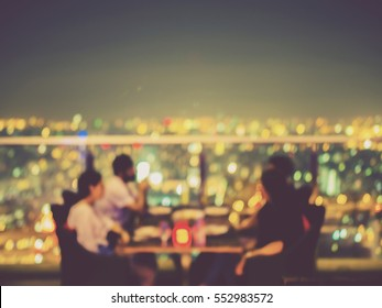 Blurred focus of rooftop restaurant with people dinning at night, vintage filtered