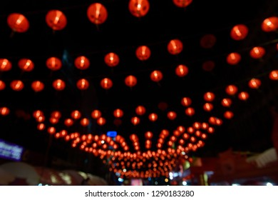 Blurred focusing on red chinese lanterns are decorated during Chinese New Year night festival on Yaowarat Road (Chinatown), Bangkok, Thailand. (Low Angle)