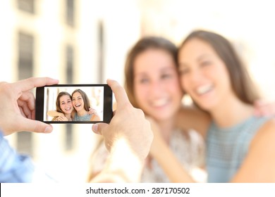 Blurred friends taking photos with a smart phone and showing the photo in the screen on the street