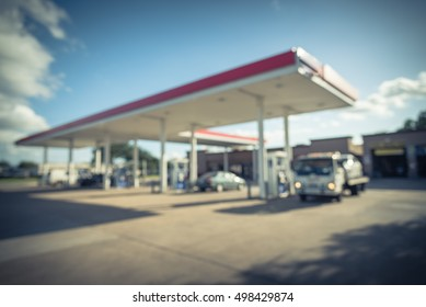 Blurred of gas station with car fill up fuel in daytime. Defocused, out of focus gas station in the morning. Abstract blur petrol station background with copy space. Vintage filter look.