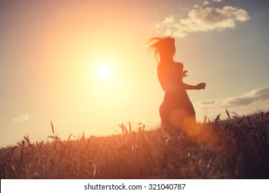 Blurred girl running in the field at sunset (intentional sun glare and lens flares, lens focus on wheat, girl in blur)