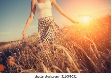 A blurred girl running through the wheat field at sunset (intentional sun glare, lens focus on wheat spikes)
