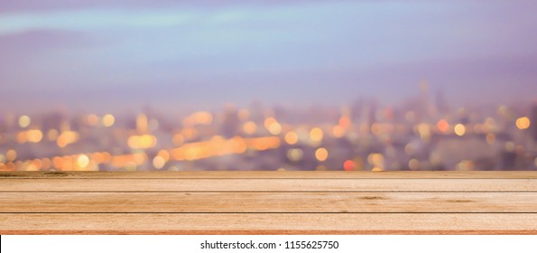 Blurred glowing night city panorama scene background with wood panels perspective for show promote product concept.
