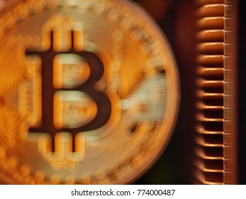 Blurred golden bitcoin BTC coin with cooling hardware background, macro closeup. Blockchain investment technology concept.