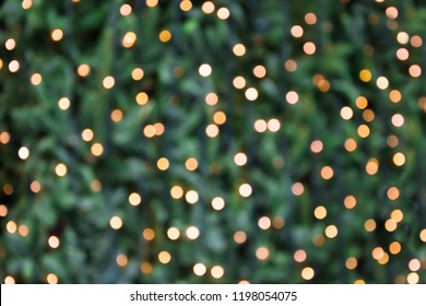 Blurred golden garland on Christmas tree, defocused background. Christmas abstract.