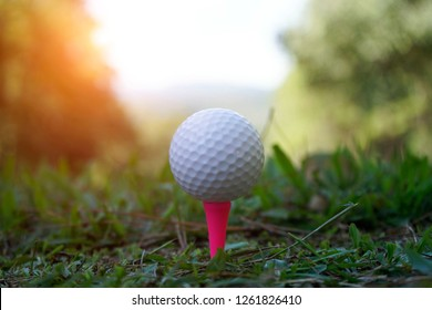 Blurred golf ball on tee in the evening golf course with sunshine in thailand