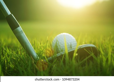 Blurred golf club and golf ball close up in grass field with sunset. Golf ball close up in golf coures at Thailand