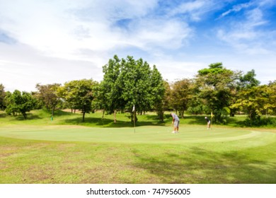 Blurred golf players on course with bright day for background.