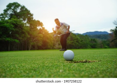 Blurred golfer playing golf in the evening golf course, on sun set evening time. Man playing golf on a golf course in the sun.