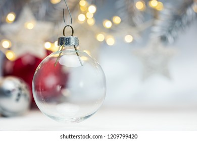 blurred grey background with glowing garlands and fir branch, focus on glass christmas ball
