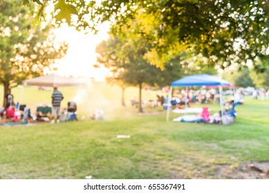 Blurred group of African American friend, family members enjoy barbecue on camping in urban park in Houston, Texas, US at sunset. BBQ grill with meat skewers smoke. Outdoor Party and Picnic Concept.