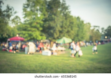 Blurred group of African American friend, family members enjoy barbecue on camping in urban park downtown Houston, Texas, US. BBQ grill meat skewers smoke. Outdoor Party, Picnic Concept. Vintage tone.
