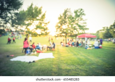 Blurred group of African American friend, family members enjoy free outdoor music festival, open-air concert held in public park at Houston. Audience sits on the chairs, grass, open tent. Vintage tone