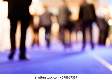 Blurred of group of businessmen walking on job fair; note shallow depth of field