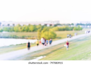 Blurred group of energetic people jog, walk, run, push stroller and bike through pathway with green tree, grass in city park at Houston, Texas, US. Abstract motion outdoor exercise. Healthy lifestyle