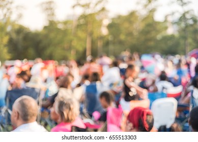 Blurred group of mixed race, ethnic, diverse culture audience sitting on grass, chair, tent on a hillside and enjoy outdoor music festival, open-air concert held in public park at downtown Houston, TX