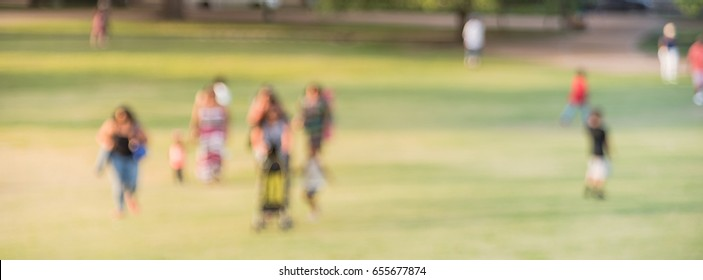 Blurred group of mixed race, ethnic, diverse culture friend and family members walking uphill in urban park at Houston, Texas, US. Down view people walk across grass hill at sunset. Panorama style