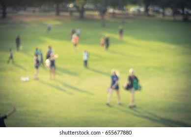 Blurred group of mixed race, ethnic, diverse culture friend and family members walking uphill in urban park at Houston, Texas, US. Down view people walk across grass hill at sunset. Vintage tone.