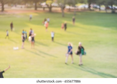 Blurred group of mixed race, ethnic, diverse culture friend and family members walking uphill in urban park at Houston, Texas, US. Down view people walk across grass hill at sunset. Healthy lifestyle.