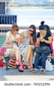 Blurred group of modern beautiful ladies using their mobiles outdoor