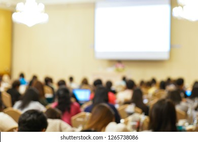 Blurred group of people sitting in seminar conference room with white screen