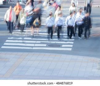blurred group of people walking on crosswalk