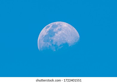 Blurred half moon on blue sky and clear clouds on daytime