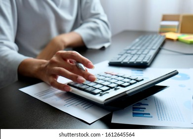 Blurred hand of Asian woman pressing calculate for prepare information of report to correct. Still holding a paper work of chart to recheck, analyze data for making presentation meeting or discussion