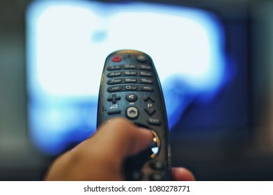 Blurred of hand holding remote of TV