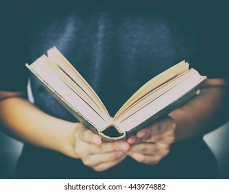 Blurred hand woman holding open book with low key scene in vintage color