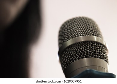blurred of hands holding businesspeople speaking with microphones in seminar, talking conference hall light with microphone and keynote. Speech is vocalized form of communication humans.