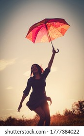 Blurred Happy girl is dancing with red umbrella in painterly sunset light. Film photo colors imitation.
