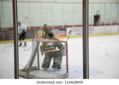 Blurred hockey players behind Plexiglas at a hockey rink