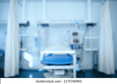 Blurred hospital room with empty bed surrounded by equipment, unfocused background.