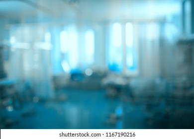 Blurred hospital room with the several beds separated by a screen, unfocused background.