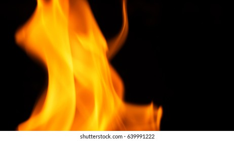 Blurred hot danger fire blazing and yellow color and black background.