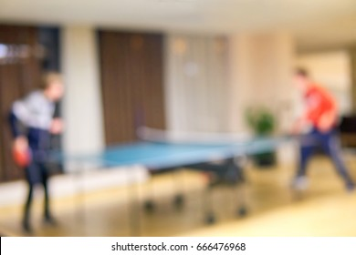 Blurred the hotel has a spacious bright lobby. Silhouettes of table tennis teenagers. Ski resort