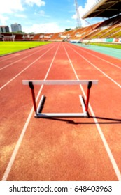 blurred hurdle race barrier on red  running track , athletic stadium , out of focus