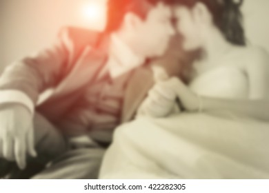 blurred iamge of couple love at wedding dress kiss and soft flare sepia tone