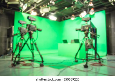 Blurred image against television green studio with camera.