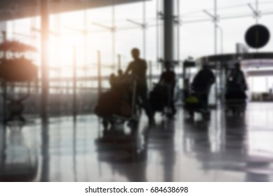 Blurred image of airline passengers carrying their luggages pass the entrance at the airport,traveling and transportation concept,copy space.