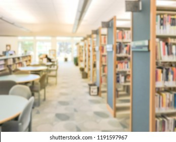Blurred image aisle of bookshelf with reading tables at public library in Texas, America. Continuing education concept.