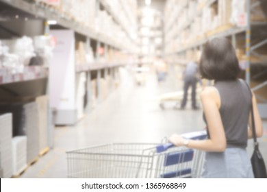 Blurred image of An asian woman doing shopping  and walking with her cart in cargo or warehouse. Boxes on rows of shelves in warm light warehouse background.  Using for Mock up template for display.