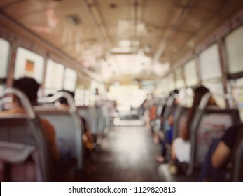Blurred image of from the back seat inside of the bus and people sitting and standing in bus, rush hour in the morning, Bangkok, Thailand. Public transportation & tourism concept. vintage film filter.