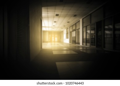 Blurred image for background long empty building corridor with dark tone style.