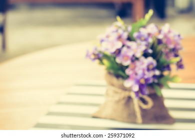 Blurred image as background from small purple flowers in jute bag on the table - vintage style color effect
