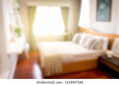 Blurred image of bed room in the morning with sun light from the window.