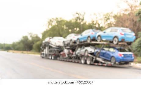 Blurred image a big car carrier truck of new cars for batch delivery to dealership. Full load transport truck of new vehicles on country road. Automotive industry abstract background. Panorama style.