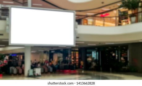 Blurred image of big television with empty white screen in shopping mall department store. Clipping path and copy space for text and advertising.